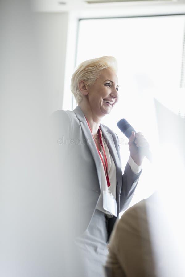 Download Lycklig Affärskvinna Som Talar Till Och Med Mikrofonen Under Seminarium Fotografering för Bildbyråer - Bild av färg, samarbete: 78726181