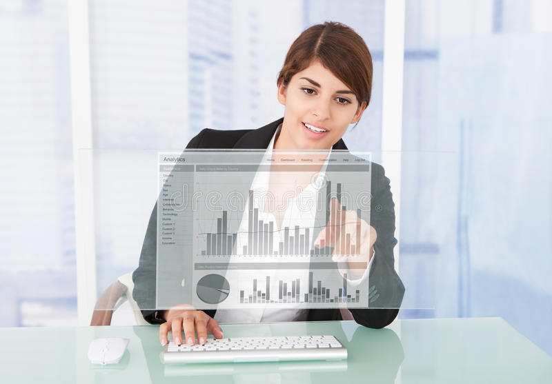 Lycklig affärskvinna Working On Graph på datorskrivbordet royaltyfri foto