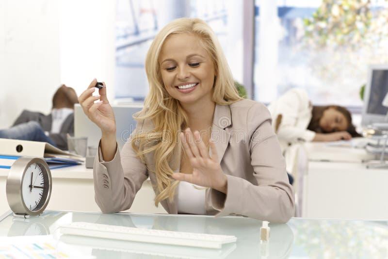 Lycklig affärskvinnapolering spikar i regeringsställning royaltyfri foto