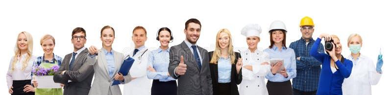 Lycklig affärsman över yrkesmässiga arbetare arkivbild