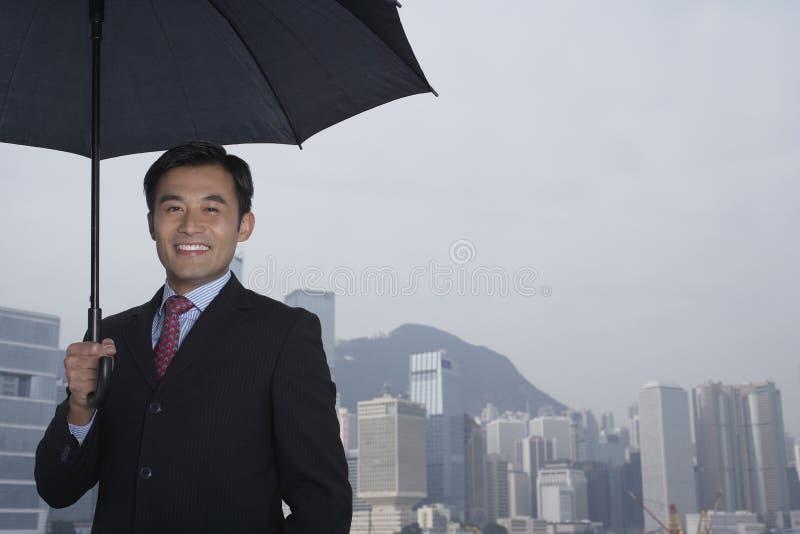 Lycklig affärsman Holding Umbrella Outdoors arkivfoto