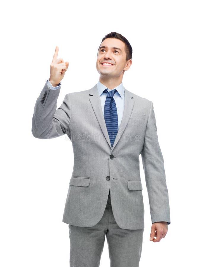 Lycklig affärsman i dräkt som pekar upp fingret arkivfoton