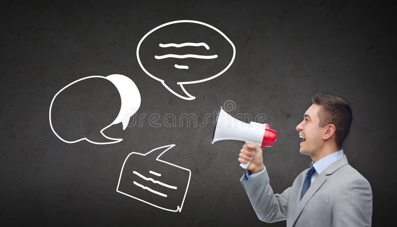 Lycklig affärsman i dräkten som talar till megafonen royaltyfri bild