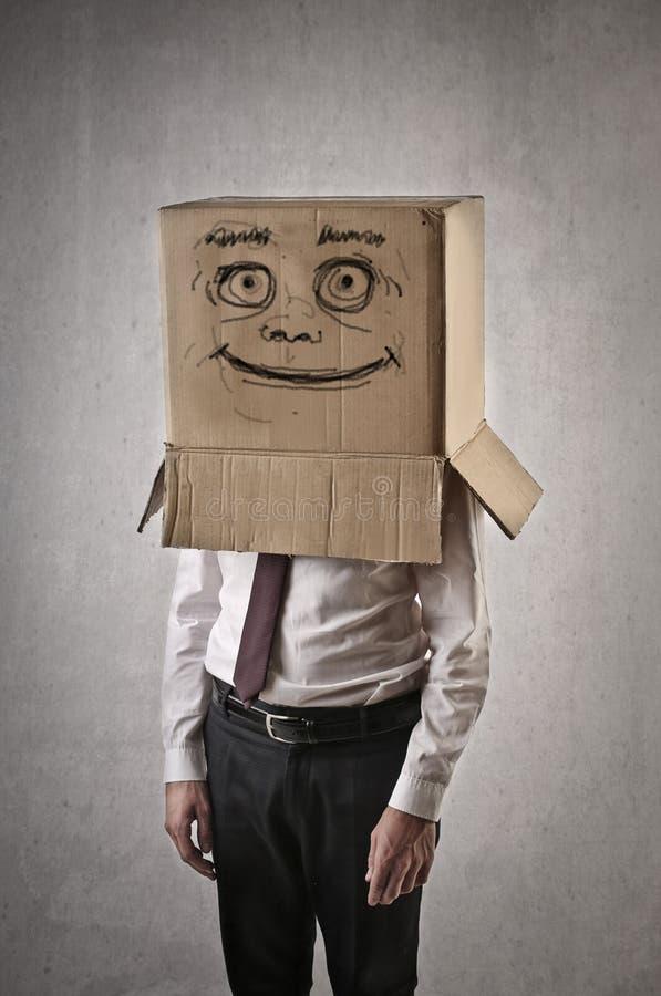 Lycklig affärsman med en ask på hans huvud royaltyfri fotografi