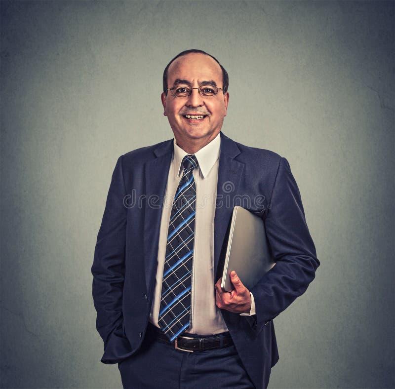 Lycklig affärsman med exponeringsglas och bärbar datoranseende på grå bakgrund arkivfoto