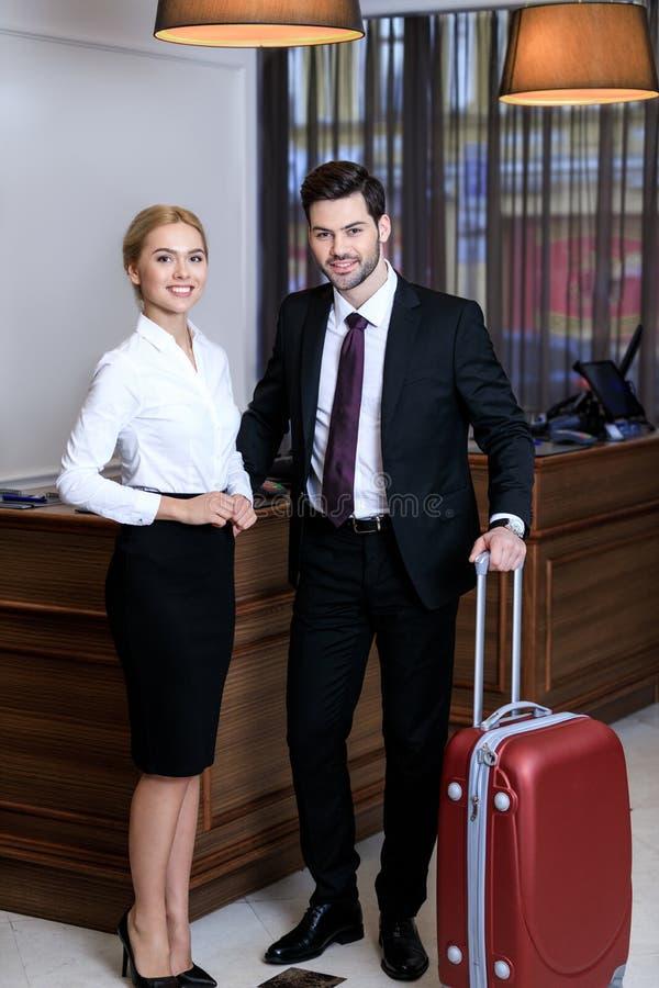lycklig affärsman och affärskvinna nära mottagandeskrivbordet royaltyfria bilder