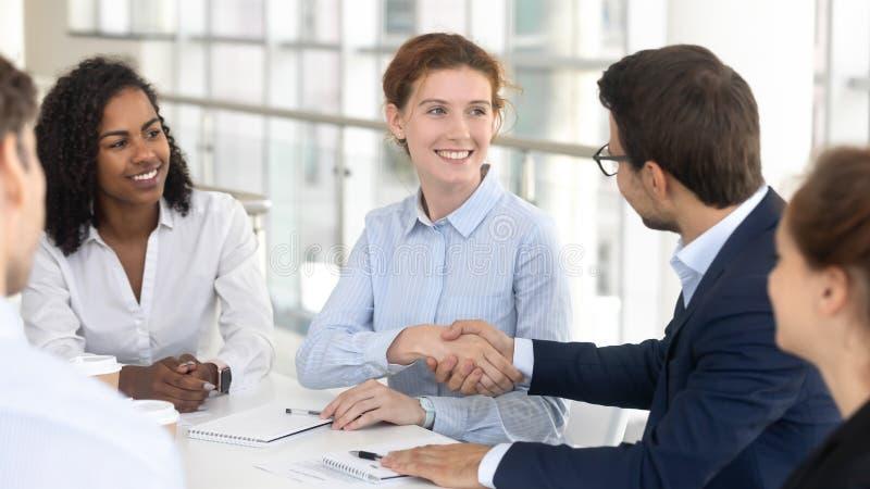 Lycklig affärsman- och affärskvinnahandskakning på laget som möter förhandling arkivfoto