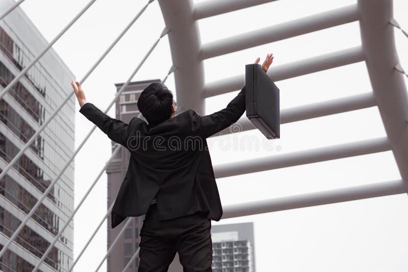 Lycklig affärsman och lönelyfthand för framgångbegreppet, baksidasikt royaltyfria bilder