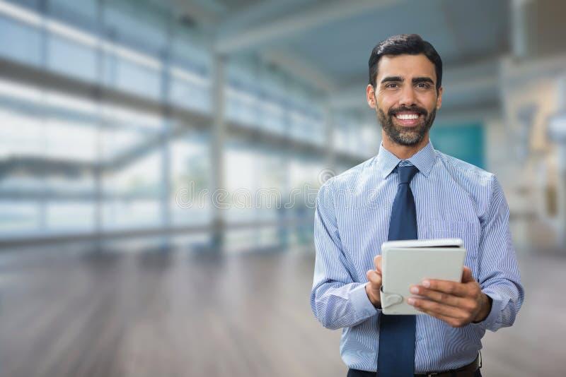 Lycklig affärsman som använder en minnestavla mot kontorsbakgrund arkivfoto