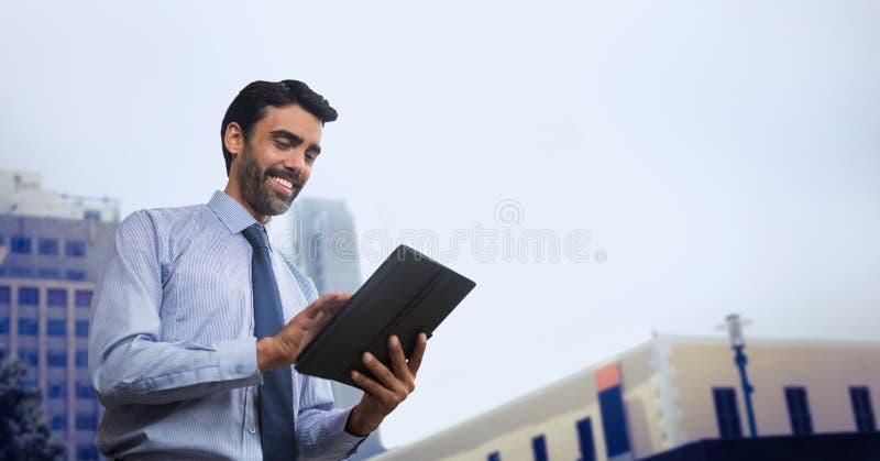 Lycklig affärsman som använder en minnestavla mot stadsbakgrund arkivfoton