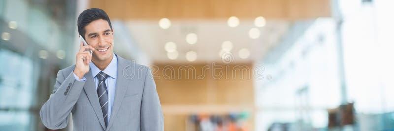 Lycklig affärsman som använder en telefon arkivbild