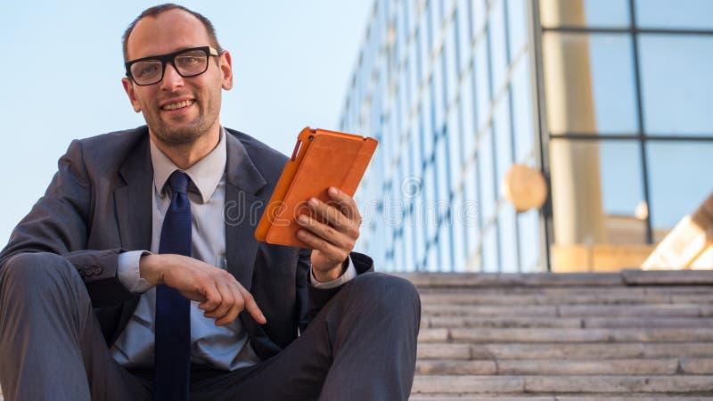Lycklig affärsman som använder minnestavlaPC i orange räkning på en stadsstr arkivbilder