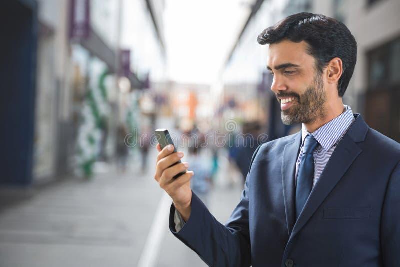 Lycklig affärsman som använder telefonen mot gatabakgrund royaltyfria bilder