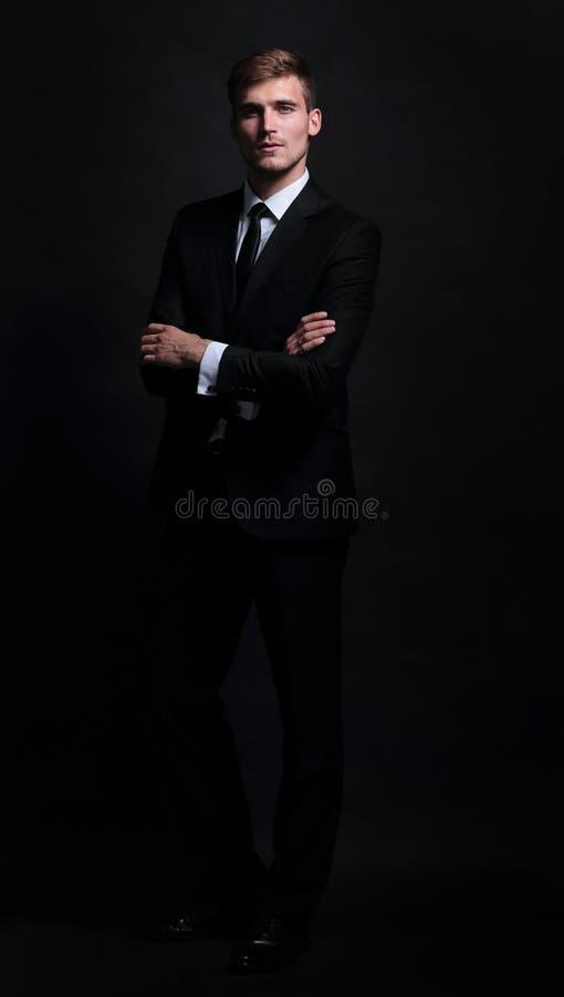 Lycklig affärsman som bär svarta dräktanseende- och vikningarmar royaltyfria bilder