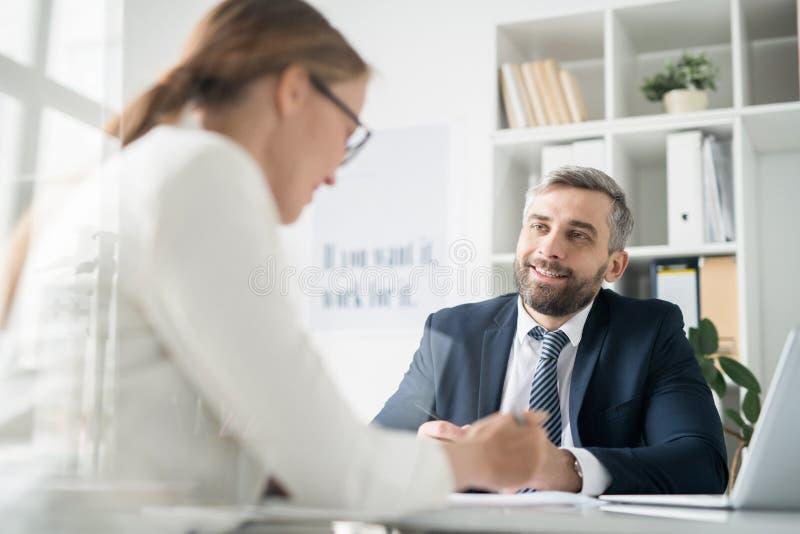Lycklig affärsman som diskuterar arbetsfrågor med kollegan royaltyfri fotografi