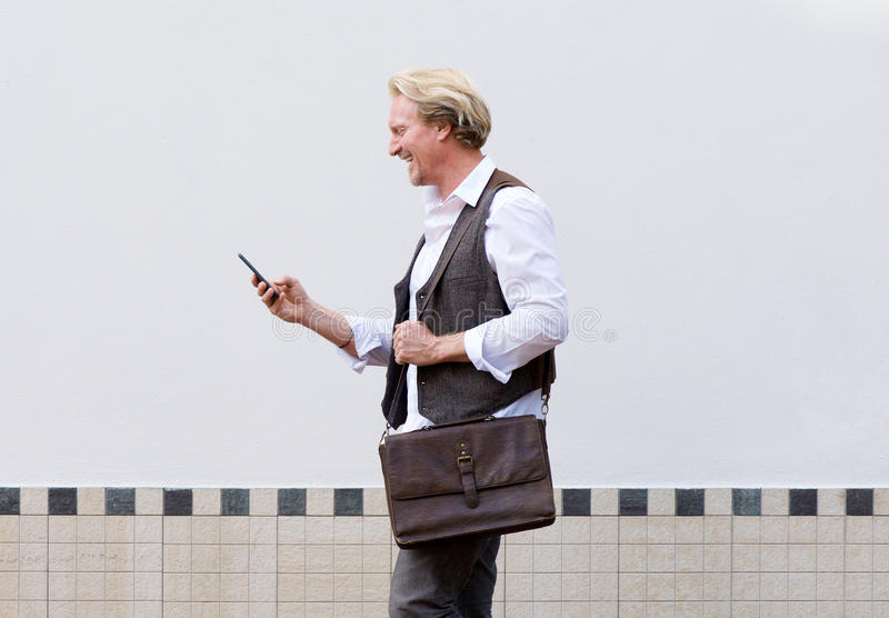 Lycklig affärsman som går med mobiltelefonen och påsen royaltyfri fotografi
