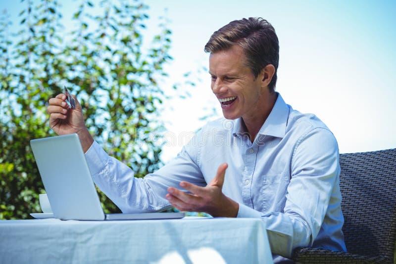 Lycklig affärsman som gör online-shopping med bärbara datorn och kreditkorten royaltyfria foton