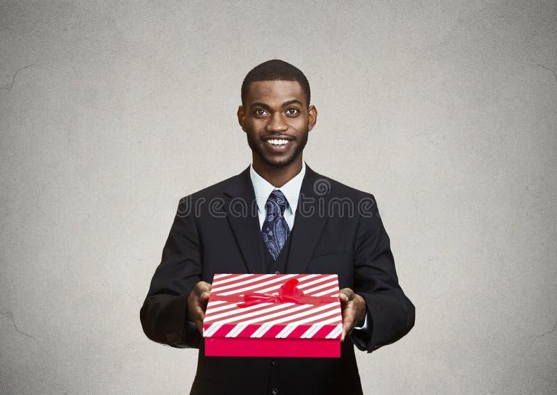 Lycklig affärsman som ger gåvaasken till någon royaltyfri bild