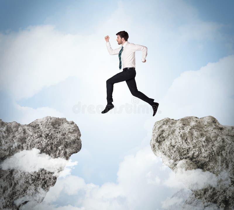 Lycklig affärsman som hoppar över en klippa royaltyfria bilder