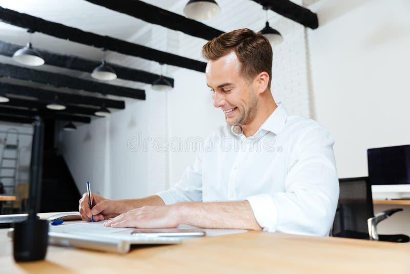 Lycklig affärsman som ler och skriver på tabellen arkivfoto