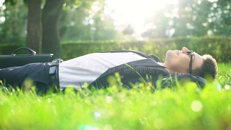 Lycklig affärsman som ligger på gräs och kopplar av efter strävsam inre harmoni royaltyfria bilder