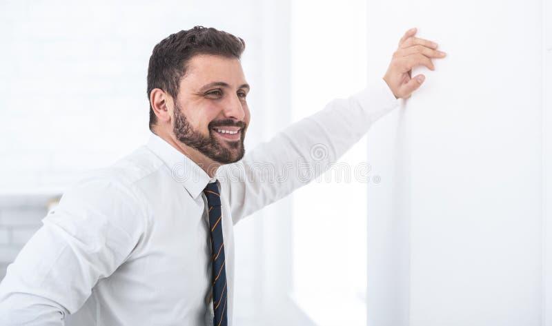 Lycklig affärsman som lutar på väggen som framåt stirrar fotografering för bildbyråer
