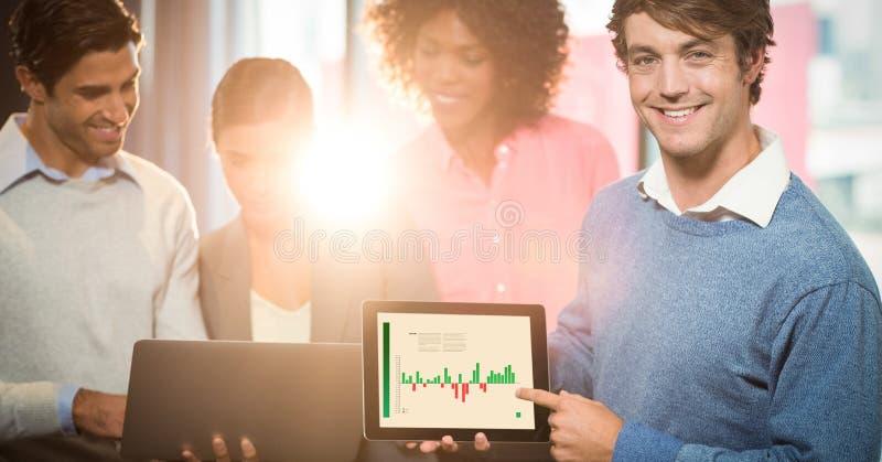 Lycklig affärsman som pekar grafen på den digitala minnestavlan med kollegor i bakgrund royaltyfri foto