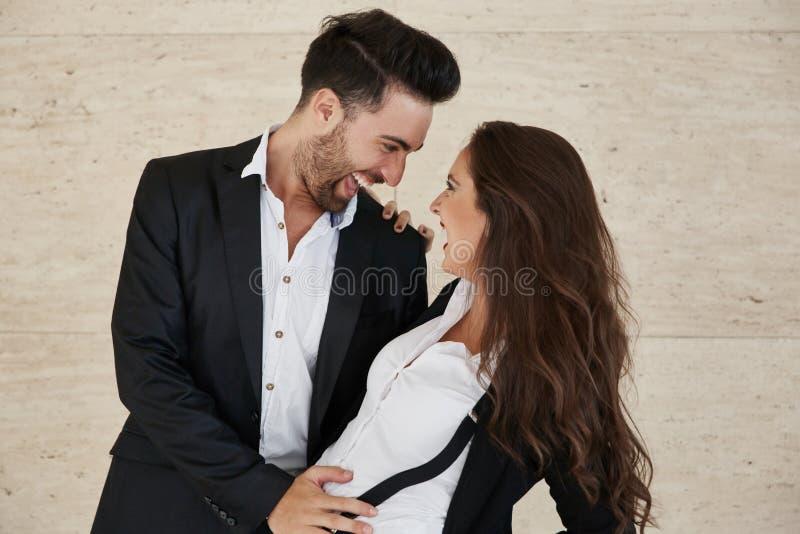 Lycklig affärsman som rymmer hans skratta för flickvän arkivbild