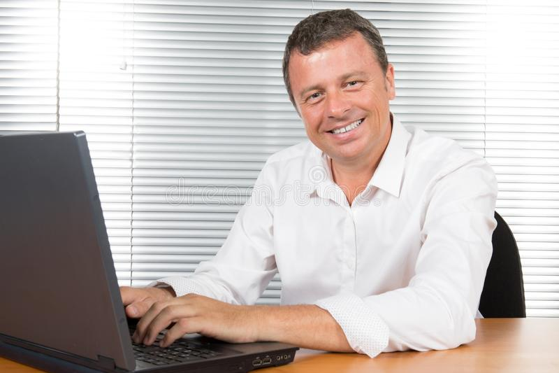 Lycklig affärsman som ser kameran med tillfredsställelse på kontoret arkivbilder