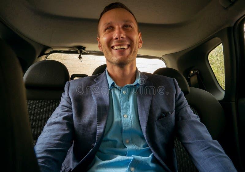 Lycklig affärsman som sitter i lyxig bil Bärande affärsdräkt för ung skäggig man genom att använda hans smartphone fotografering för bildbyråer