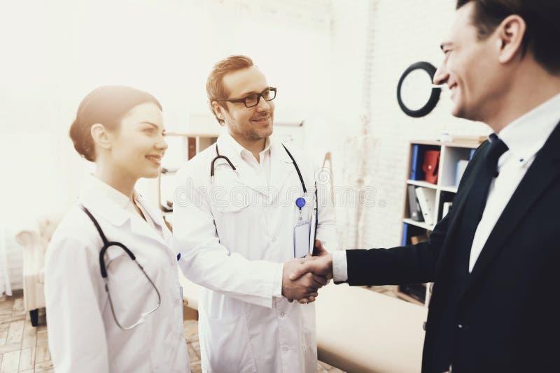 Lycklig affärsman som skakar händer med doktorn som kurerade krämpa _ arkivfoto