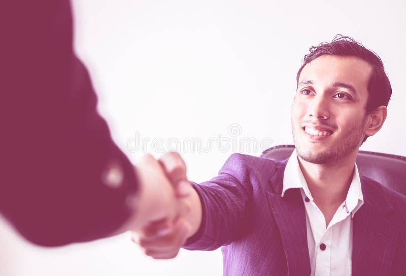 Lycklig affärsman som skakar handen som stänger avtalet med leende royaltyfri bild