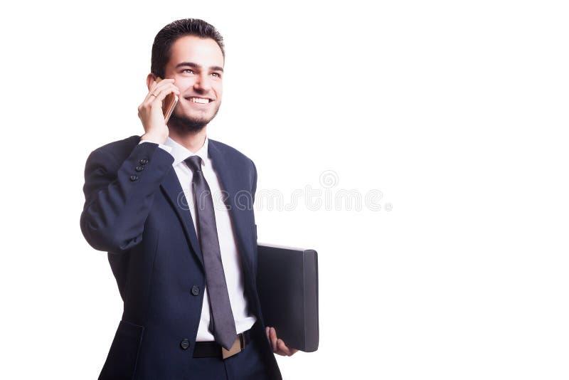 Lycklig affärsman som talar på telefonen med mappen i hand royaltyfri foto