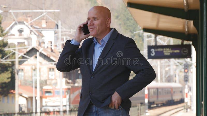 Lycklig affärsman Talking till mobiltelefonen i en drevstation royaltyfria foton