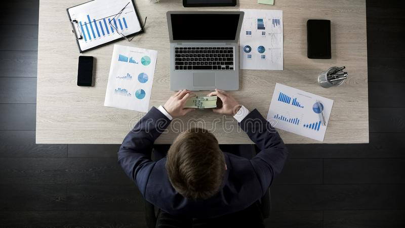 Lycklig affärsmaninnehavbunt av pengar, belöning för lyckat projekt arkivfoton
