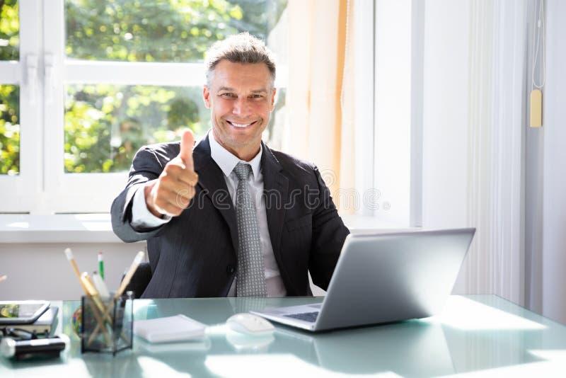 Lycklig aff?rsman Gesturing Thumbs Up royaltyfria foton