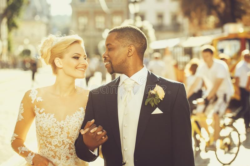 Lycklig afrikansk amerikanbrudgum och gullig brud som går på gatan royaltyfri foto