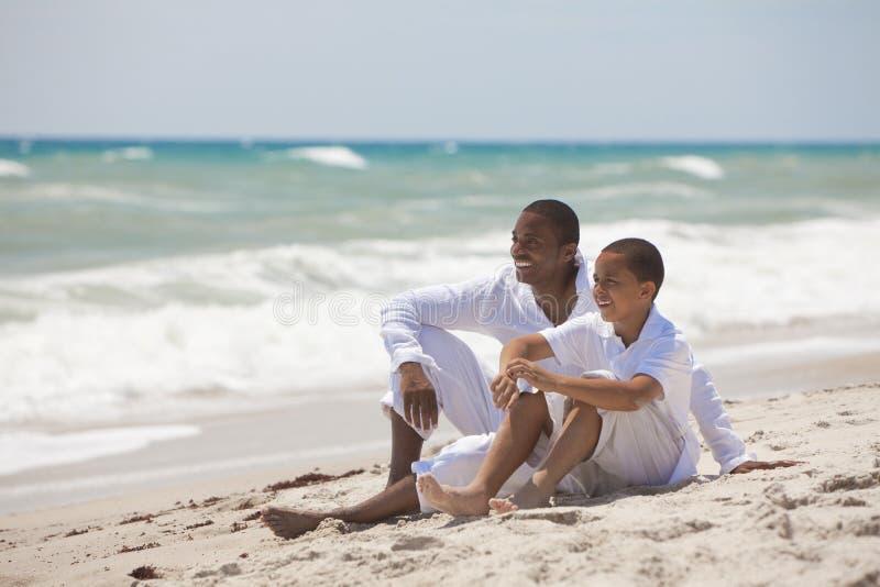 Lycklig afrikansk amerikanfader och Son på strand