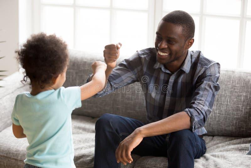 Lycklig afrikansk amerikanfader som hemma spelar med sonen royaltyfria foton