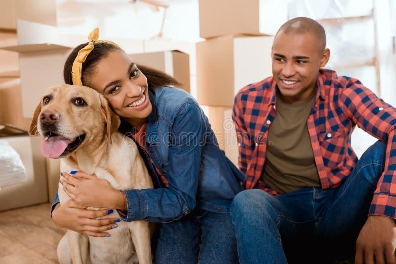 lycklig afrikansk amerikanfamilj med den labrador hunden som flyttar sig till arkivbild