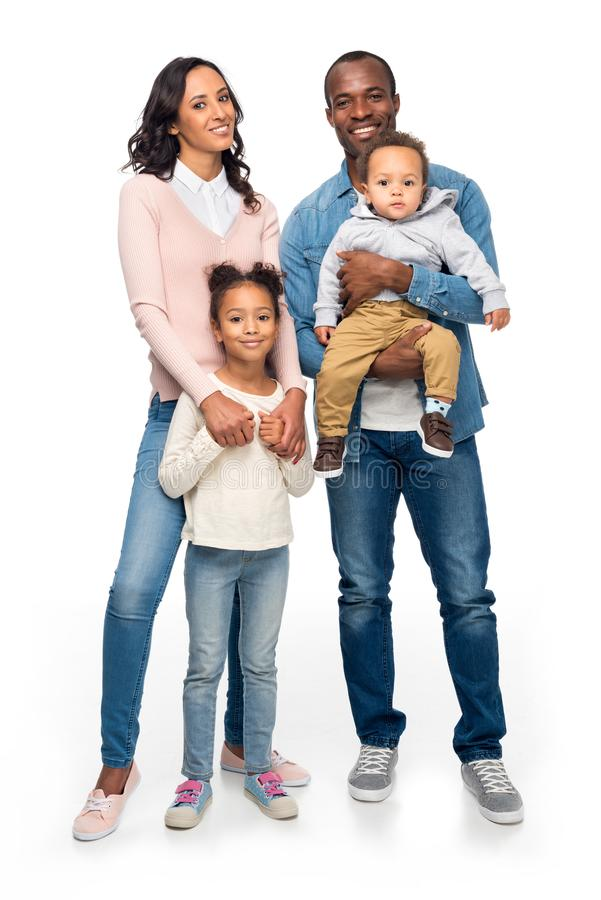 lycklig afrikansk amerikanfamilj med två ungar som tillsammans står och ler på kameran royaltyfri fotografi
