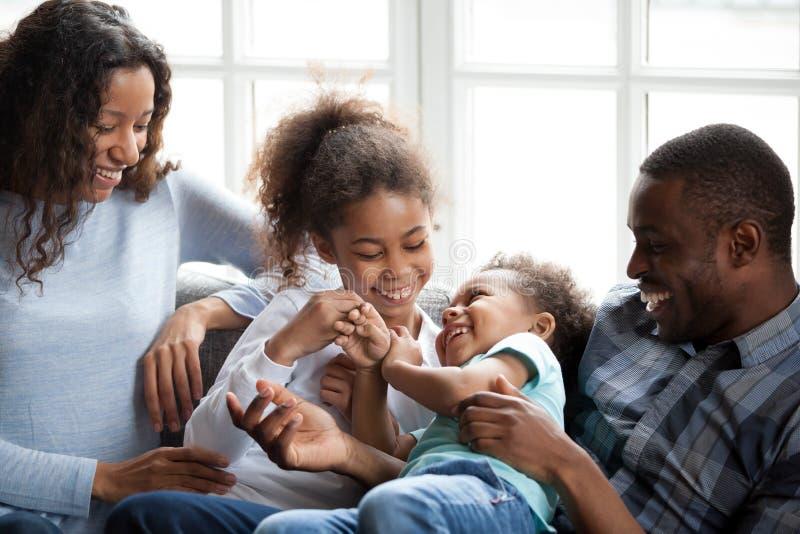 Lycklig afrikansk amerikanfamilj som hemma spelar med barn royaltyfria bilder