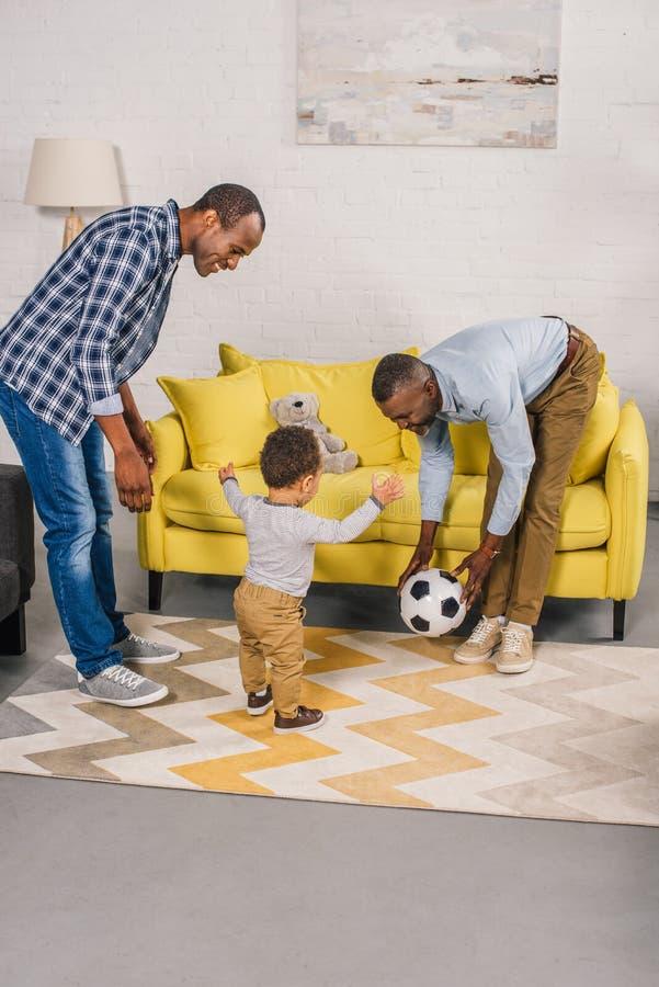 lycklig afrikansk amerikanfamilj som spelar med fotbollbollen fotografering för bildbyråer