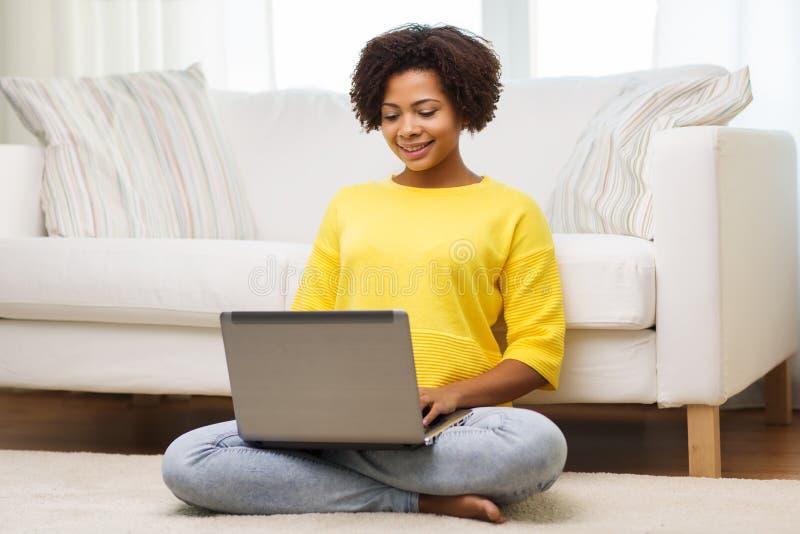 Lycklig afrikansk amerikankvinna med den hemmastadda bärbara datorn royaltyfria foton