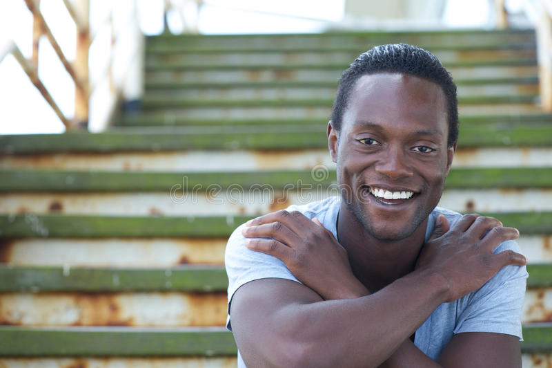 Lycklig afrikansk amerikanman som ler med korsade armar arkivbilder