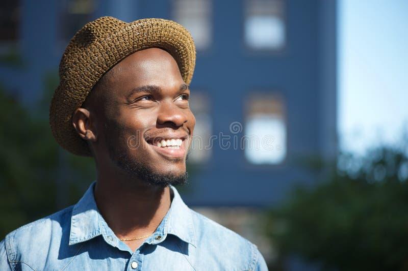 Lycklig afrikansk amerikanman som utomhus ler med hatten arkivbild