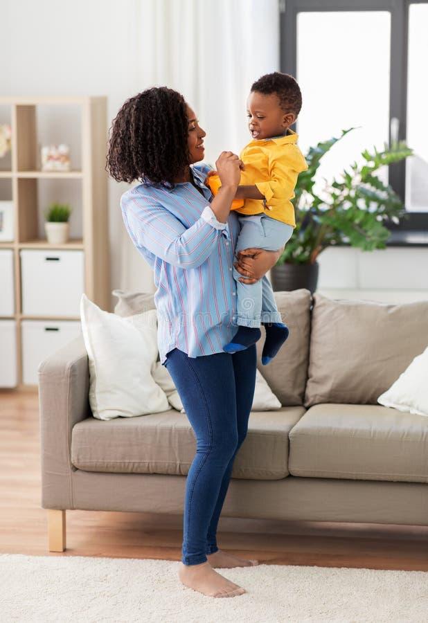 Lycklig afrikansk amerikanmoder med att behandla som ett barn hemma arkivfoton