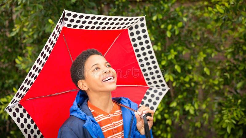 Lycklig afrikansk amerikanpojke som skrattar och att rymma paraplyet och lookin royaltyfri foto