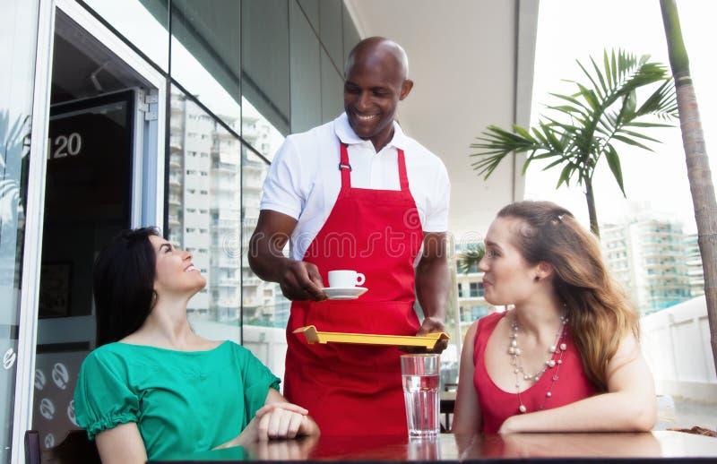 Lycklig afrikansk amerikanuppassare på arbete i en restaurang royaltyfria bilder