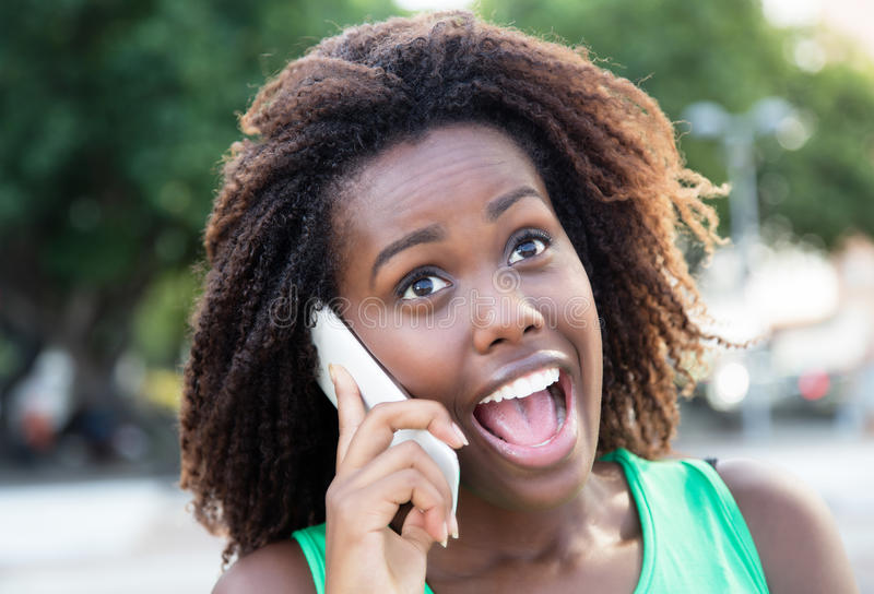 Lycklig afrikansk kvinna i en grön skjorta som är utomhus- på telefonen arkivbilder